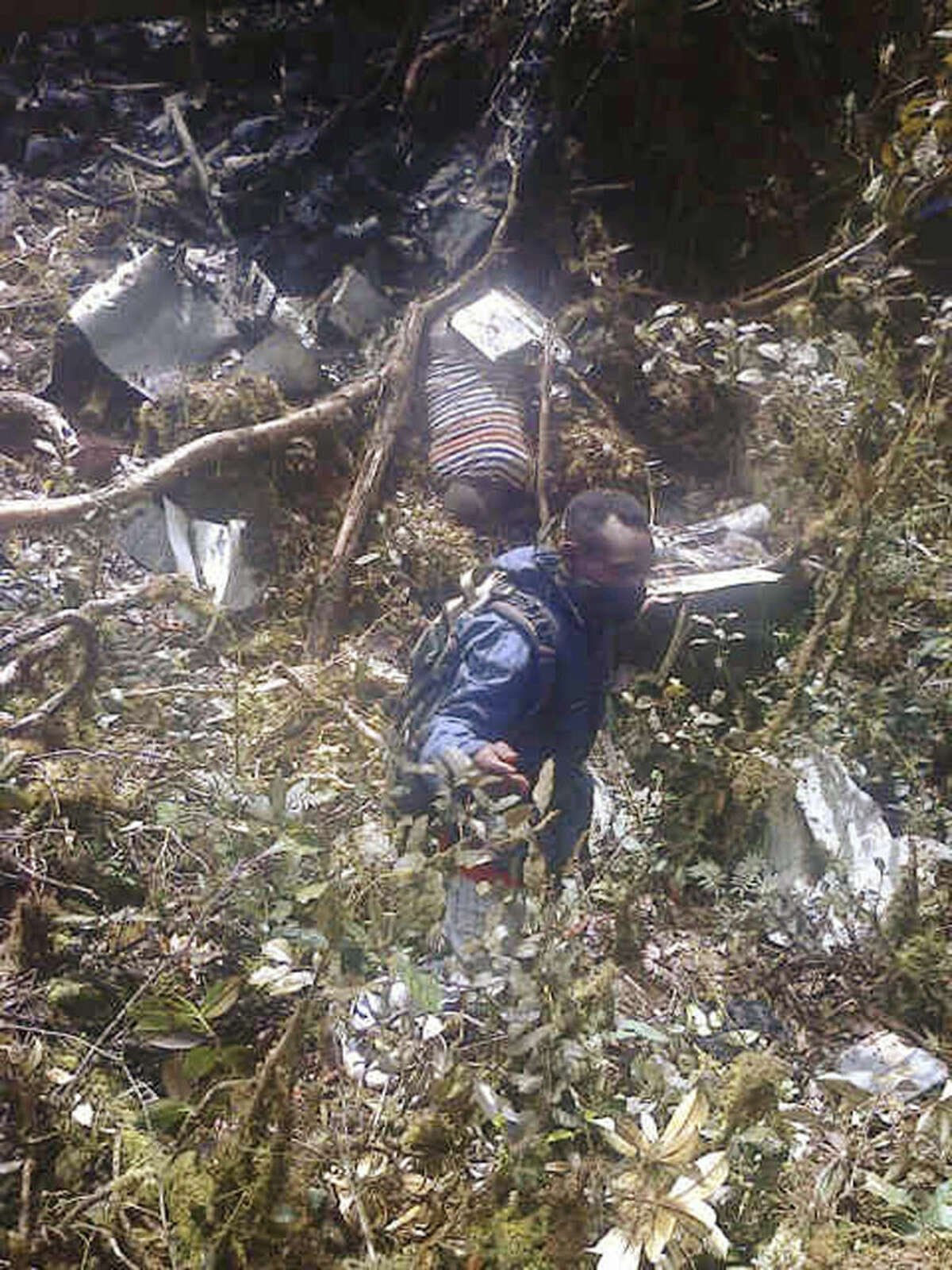 Plane wreckage is strewn across dense terrain in Pegunungan Bintang, Papua province, Indonesia, Tuesday, Aug. 18, 2015. The Trigana Air Service plane that went missing two days ago was destroyed when it slammed into a mountain, killing all 54 people on board, the country's top rescue official said.(AP Photo)