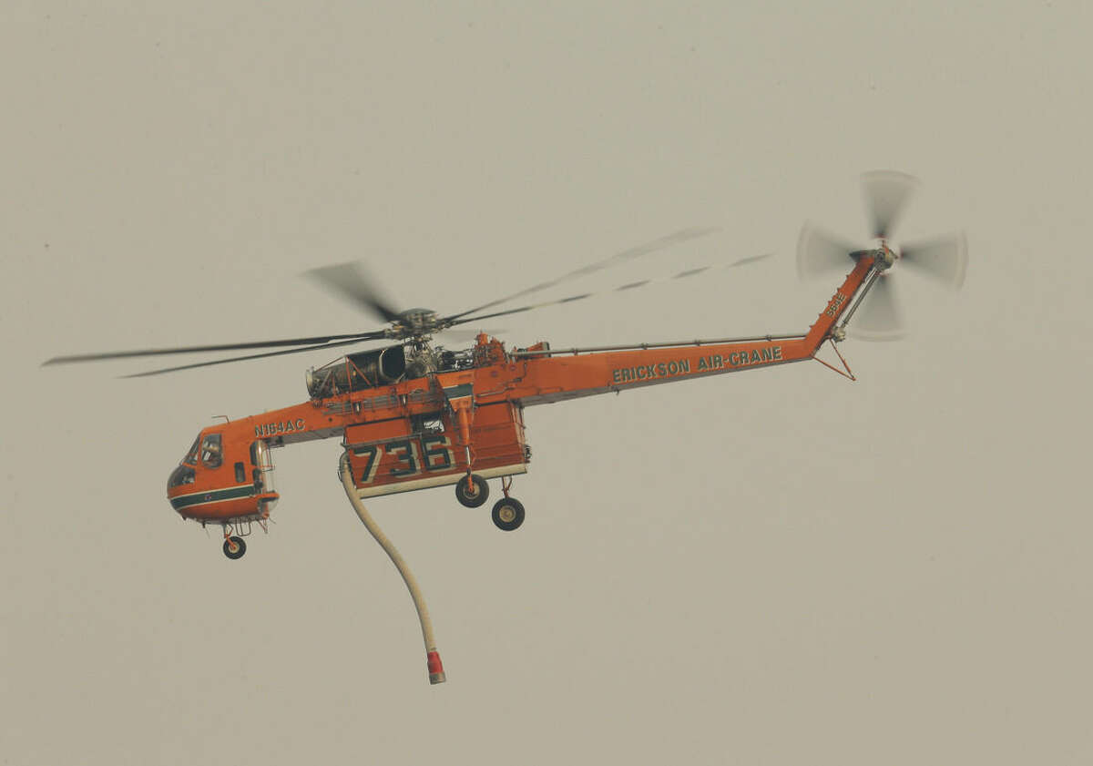 A helicopter used for fighting wildfires flies above the Columbia river, Monday, Aug. 17, 2015, outside of Chelan, Wash. Big wildfires threatened the Lake Chelan resort region of central Washington on Monday after driving away tourists, destroying a warehouse filled with nearly 2 million pounds of apples and forcing thousands of residents to flee. (AP Photo/Ted S. Warren)