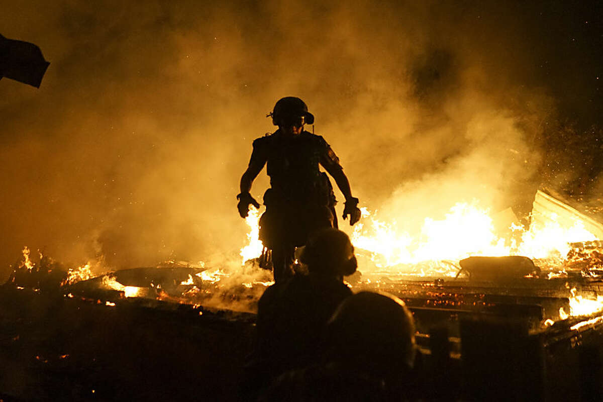 In this photo taken late Sunday, Aug. 16, 2015, firefighters extinguish fire at a house destroyed by night-long shelling in Donetsk, eastern Ukraine. A night-long artillery exchange in eastern Ukraine between government troops and Russia-backed rebels claimed nine lives on Monday, casting doubt on the already shaky cease-fire. (AP Photo/Mstyslav Chernov)