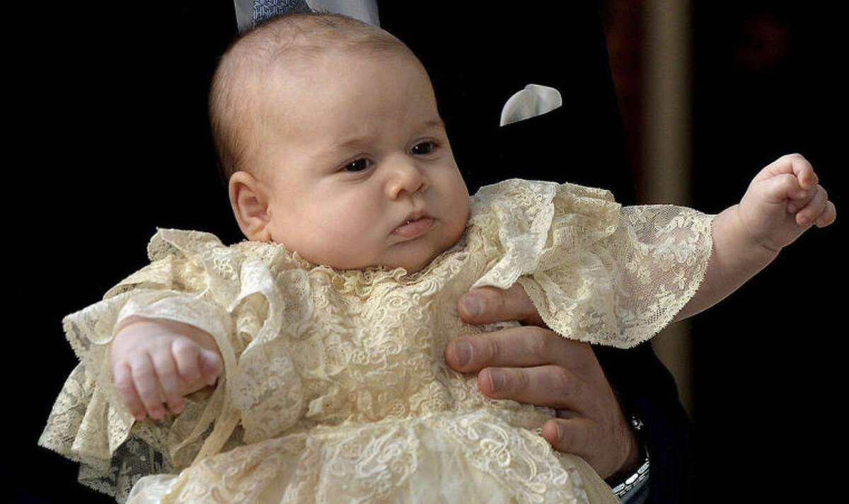 """FILE - This is a Wednesday Oct. 23, 2013 file photo of Britain's Prince George as he is held by his father Prince William as they arrive at Chapel Royal in St James's Palace in London, for the christening of the three month-old Prince. Prince George turns 1 on Tuesday. While he may be too young to appreciate it, the milestone is causing a nationwide frenzy. Editorial writers call him a symbol of hope, newspaper headlines hail him as """"Gorgeous George"""" and one published a 24-page glossy magazine chronicling his first 12 months. (AP Photo/John Stillwell/Pool, File)"""