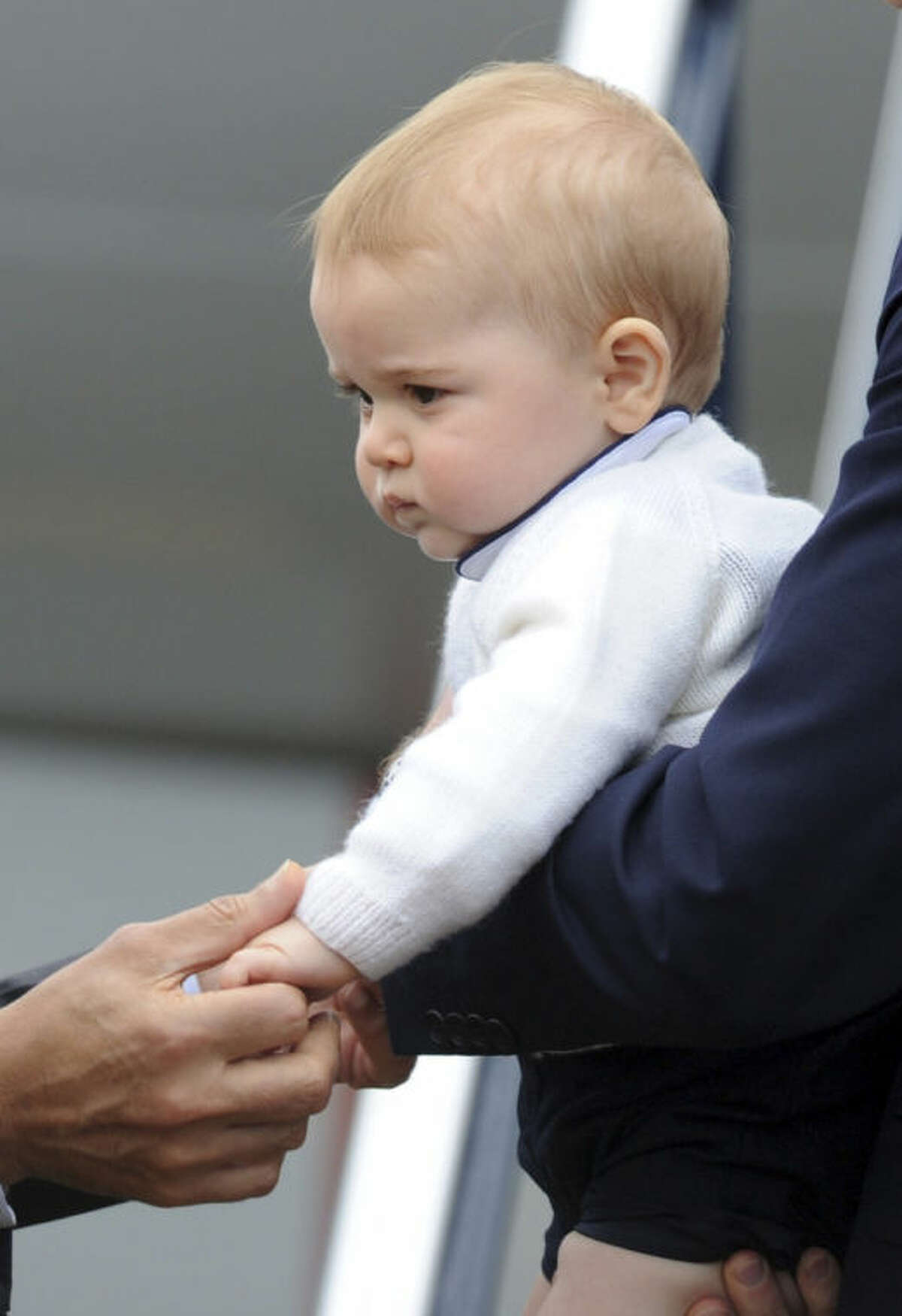 """FILE - This is a Wednesday, April 16, 2014 file photo of Britain's Prince George's as his hand is held by New Zealand Governor General Jerry Mateparae as he leaves with his parents Prince William and Kate, the Duchess of Cambridge on a plane bound for Sydney, Australia from Wellington, New Zealand. Prince George turns 1 on Tuesday. While he may be too young to appreciate it, the milestone is causing a nationwide frenzy. Editorial writers call him a symbol of hope, newspaper headlines hail him as """"Gorgeous George"""" and one published a 24-page glossy magazine chronicling his first 12 months. (AP Photo/SNPA, Ross Setford, File) NEW ZEALAND OUT"""