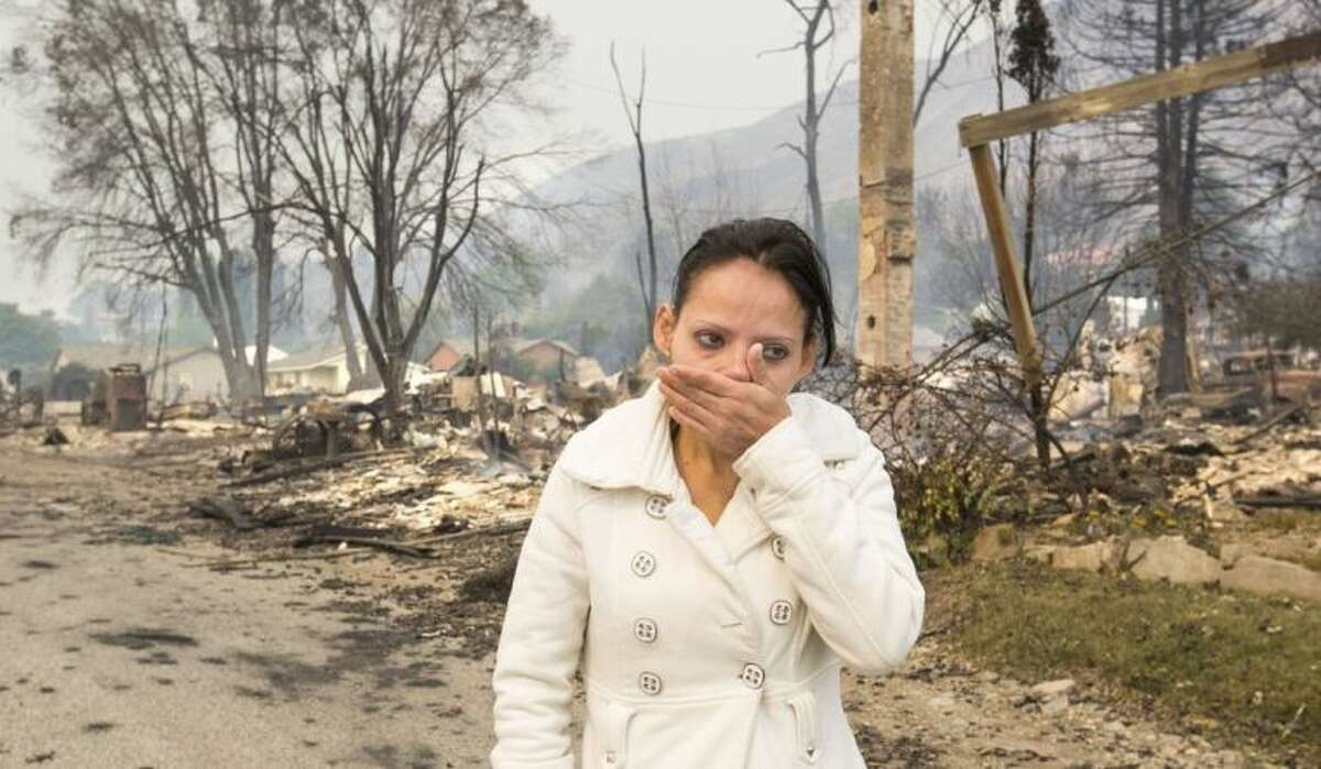 Emma Franco, views her destroyed mobile home on Friday, July 18, 2014, after several homes were destroyed in Pateros, Wash., along South Dawson Street near Warren Street on Thursday evening. Tens of thousands of acres are burning in four major fires around the state, destroying homes and forcing residents to pack up and run. (AP Photo/The Seattle Times, Mike Siegel)