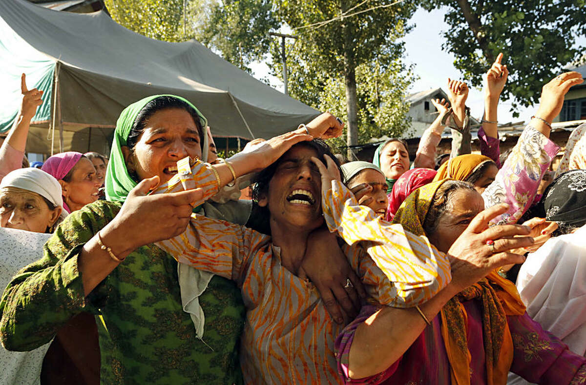 Unidentified relatives of policeman Fayaz Ahmad wail during his funeral procession at Wadoora, 60 kilometres (37 miles) from Srinagar, Indian-controlled Kashmir, Tuesday, Aug. 18, 2015. Suspected rebels opened fire at a police post in the Indian-controlled portion of Kashmir on Tuesday, killing a police constable and a civilian, authorities said. (AP Photo/Mukhtar Khan)