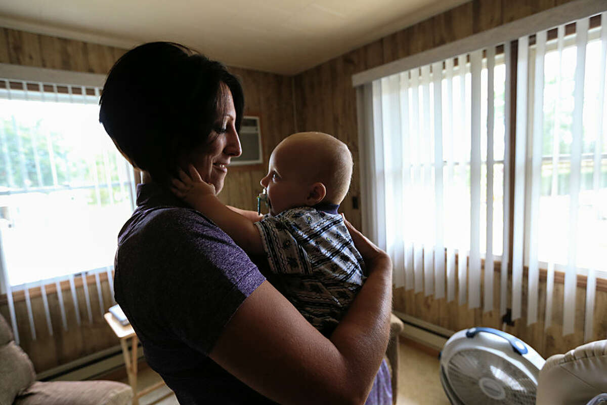 In this Thursday, Aug. 13, 2015, photo, nurse Kerri Lutjens looks over Rylan Hofer, an 8-month-old Hutterite, during a home visit at the Tschetter Colony near Olivet, S.D. Lutjens has spent the past few years gaining the trust of several communities of Hutterites, a deeply religious people, who live in insular farming communities in the Plains, Upper Midwest and Canada. (AP Photo/Nati Harnik)