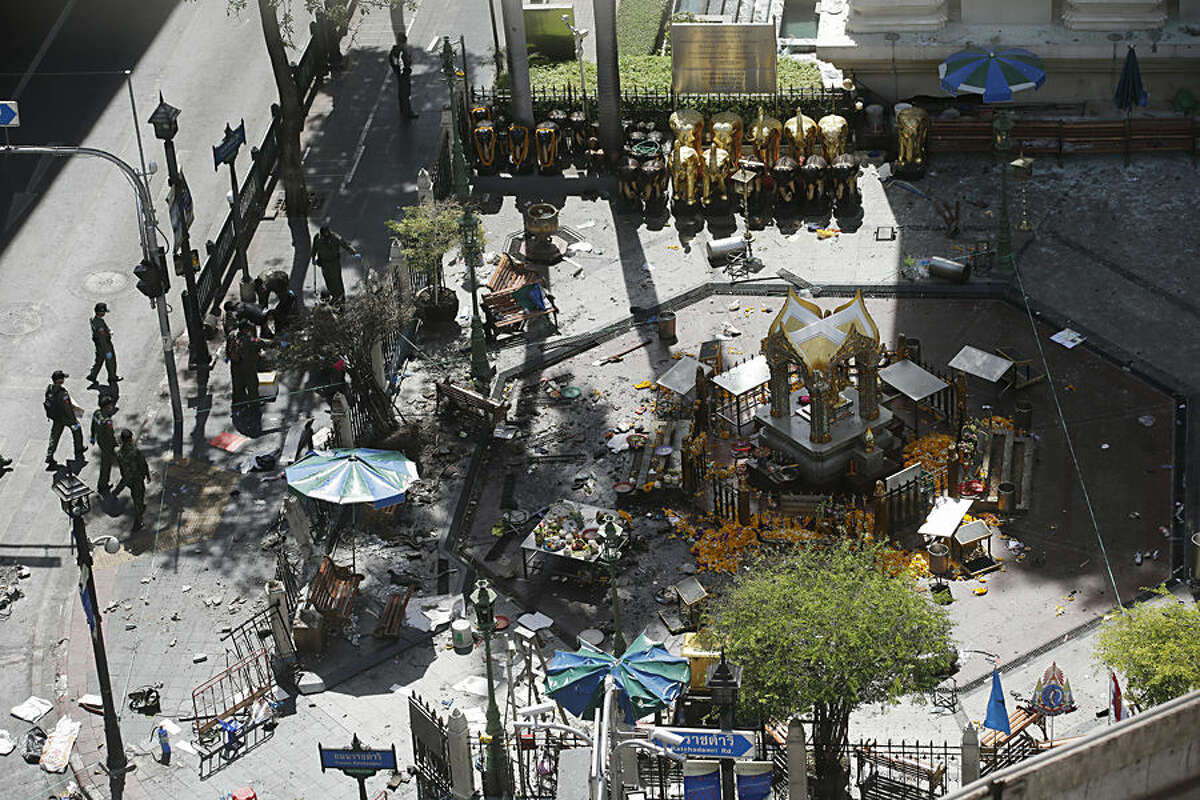 Investigators walk towards the Erawan Shrine at Rajprasong intersection in Bangkok, Thailand, Tuesday, Aug. 18, 2015, the morning after an explosion. Thailand's prime minister on Tuesday promised that authorities would quickly track down those responsible for the central Bangkok bombing, which he described as the country's worst attack ever. (AP Photo/Sakchai Lalit)