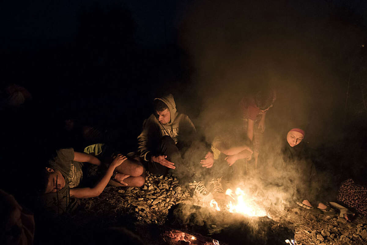 Syrian refugees warm up near fire as they wait near the border train station of Idomeni, northern Greece, to be allowed by the Macedonian police to cross the border from Greece to Macedonia, Tuesday, Aug. 18, 2015. More than 135,000 migrants have arrived on Greek islands so far this year, hoping to head north to other more prosperous European countries such as Germany, the Netherlands and Scandinavian countries. (AP Photo/Giannis Papanikos)