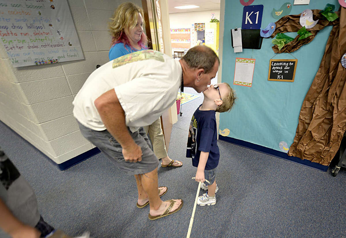 Miles Warren, 5, gives a kiss to his dad, Shane Warren, as he gets dropped off at his classroom for the first day of school, as mom DeAnne Warren, looks on at North Augusta Elementary School Monday morning Aug. 17, 2015, in North Augusta, S.C. (Michael Holahan /The Augusta Chronicle via AP)