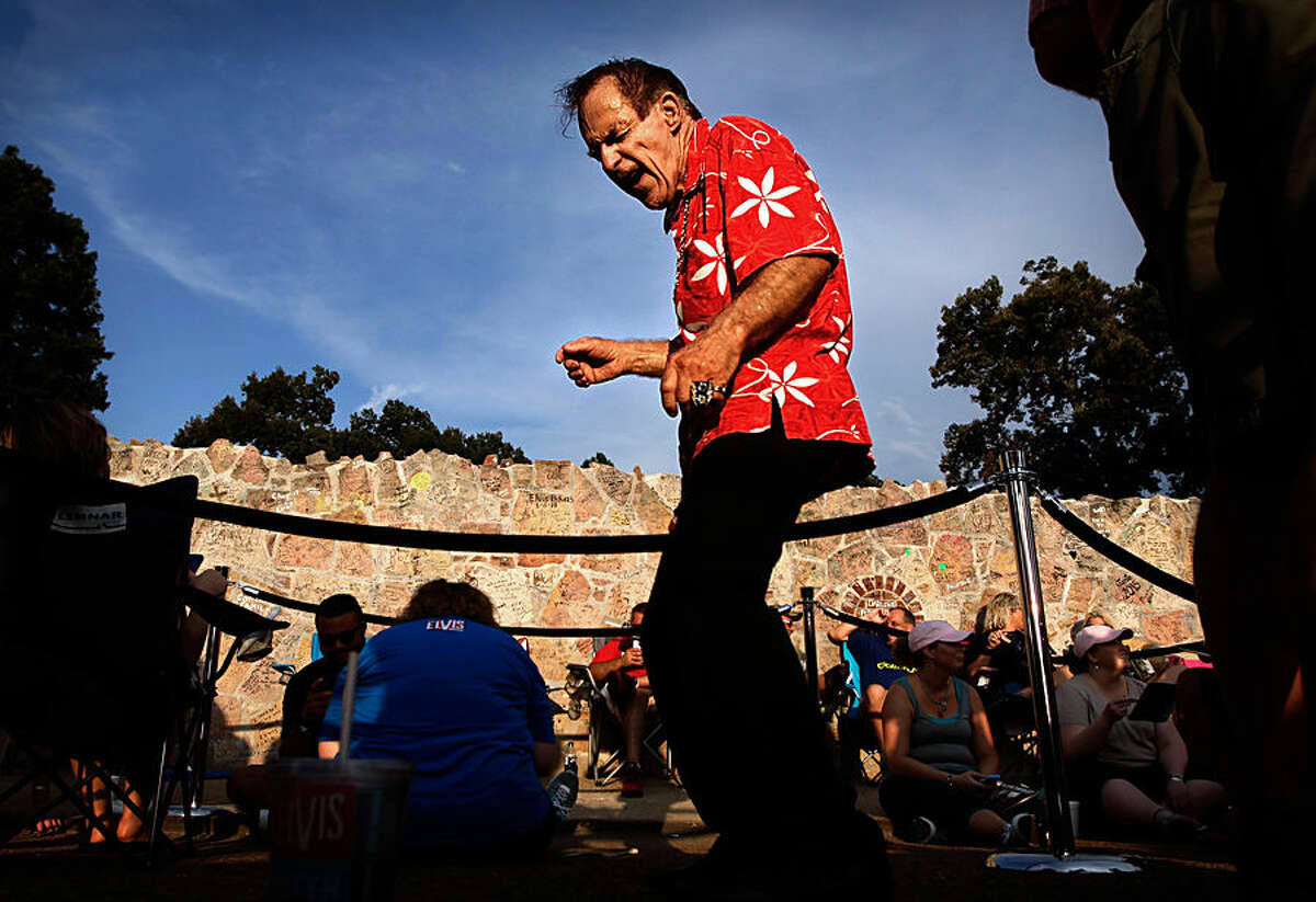 John Plant, 70, from Schenectady, NY serenades Elvis fans waiting in line in front of Graceland Saturday, Aug. 15, 2015, before a vigil to mark the 38th anniversary of the death of Elvis Presley. Thousands of Elvis fans gathered at the gates of Graceland for the annual event. (Jim Weber/The Commercial Appeal via AP)