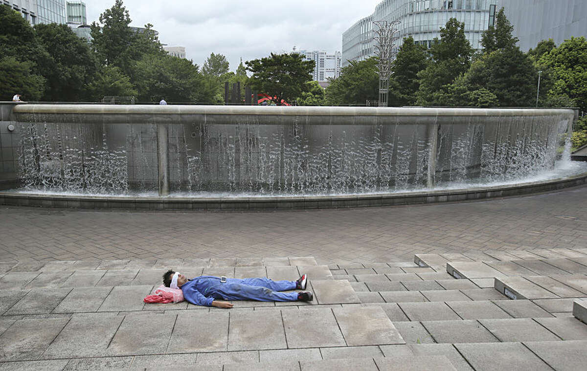 A man rests near a fountain during a lunch time in Tokyo, Monday, Aug. 17, 2015. (AP Photo/Koji Sasahara)