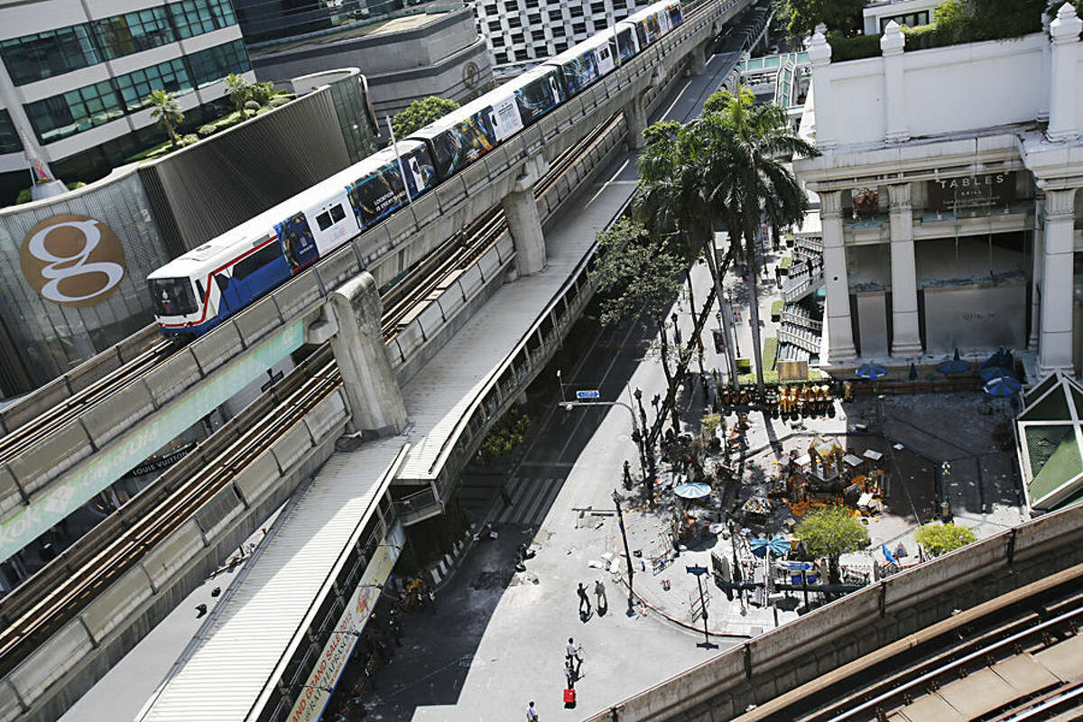 The Erawan Shrine, right, and Rajprasong intersection remains closed in Bangkok, Thailand, Tuesday, Aug. 18, 2015, as investigations continue the morning after an explosion. Thailand's prime minister on Tuesday promised that authorities would quickly track down those responsible for the central Bangkok bombing which he described as the country's worst attack ever. (AP Photo/Sakchai Lalit)