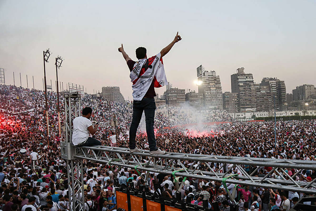 In this July 31, 2015 photo, Zamalek soccer fans celebrate after winning the Egyptian League at Zamalek Club in Cairo, Egypt. The hardcore fan base Ultras White Knights did not celebrate the winning of the team out of respect for more than 20 soccer fans who were crushed to death outside an air defense stadium in Cairo after police fired tear gas to break up the crowd waiting in a fenced, narrow corridor to watch. Police accused the fans of attacking the force, and rioting to enter the stadium on Feb. 8, 2015. (AP Photo/Mohammed El Raai)