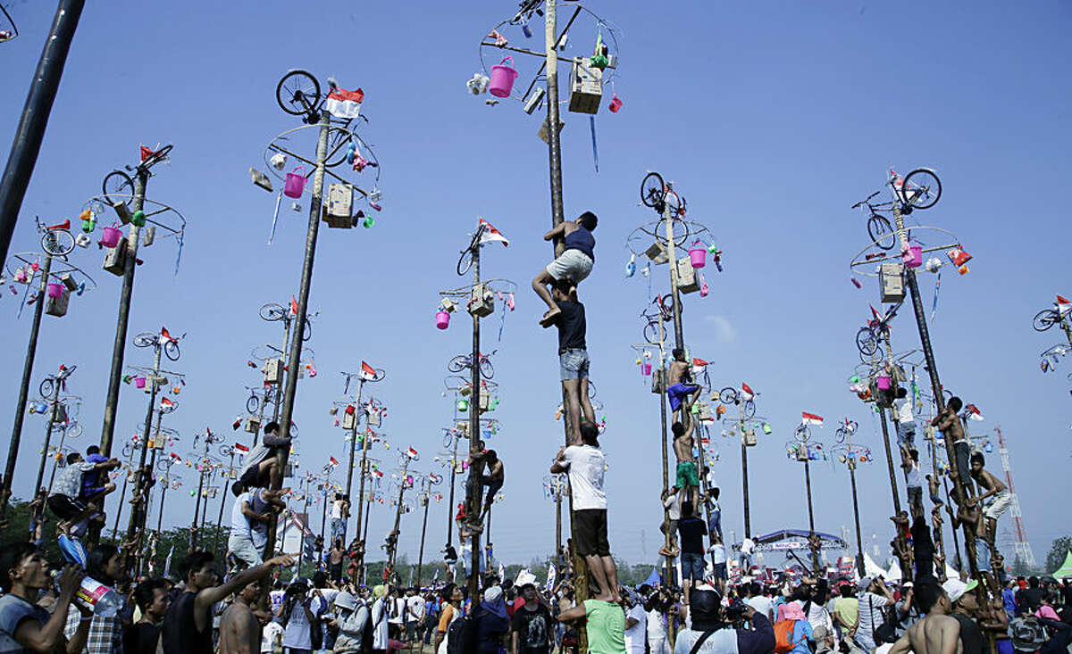 Indonesian men climb greased poles to retrieve prizes such as bicycles and rice cookers as part of the Independence Day festivities at Ancol Beach in Jakarta, Indonesia, Monday, Aug. 17, 2015. Indonesia marked the 70th anniversary of its declaration of independence from Dutch colonial rule on Monday. (AP Photo/Tatan Syuflana)