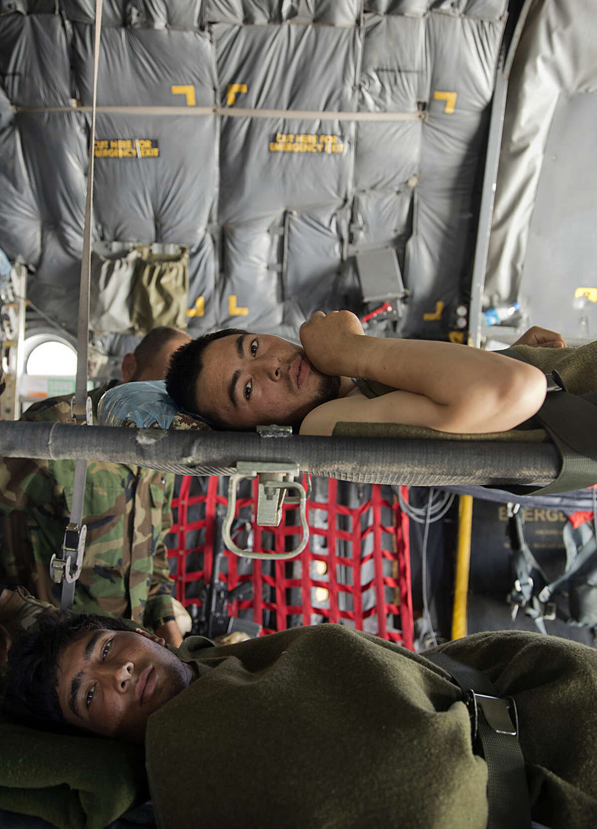 Wounded Afghanistan's National Army soldiers lie on cots, inside a C-130 Hercules aircraft, that belongs to the Afghan National Army, at Kandahar Air Field, Afghanistan, Tuesday, Aug. 18, 2015. Since the departure from Afghanistan last year of most international combat troops, Afghan security forces have been fighting the insurgency alone. Figures show that casualty rates are extremely high, reflecting an emboldened Taliban testing the commitment and strength of the Afghan military. (AP Photo/Massoud Hossaini)
