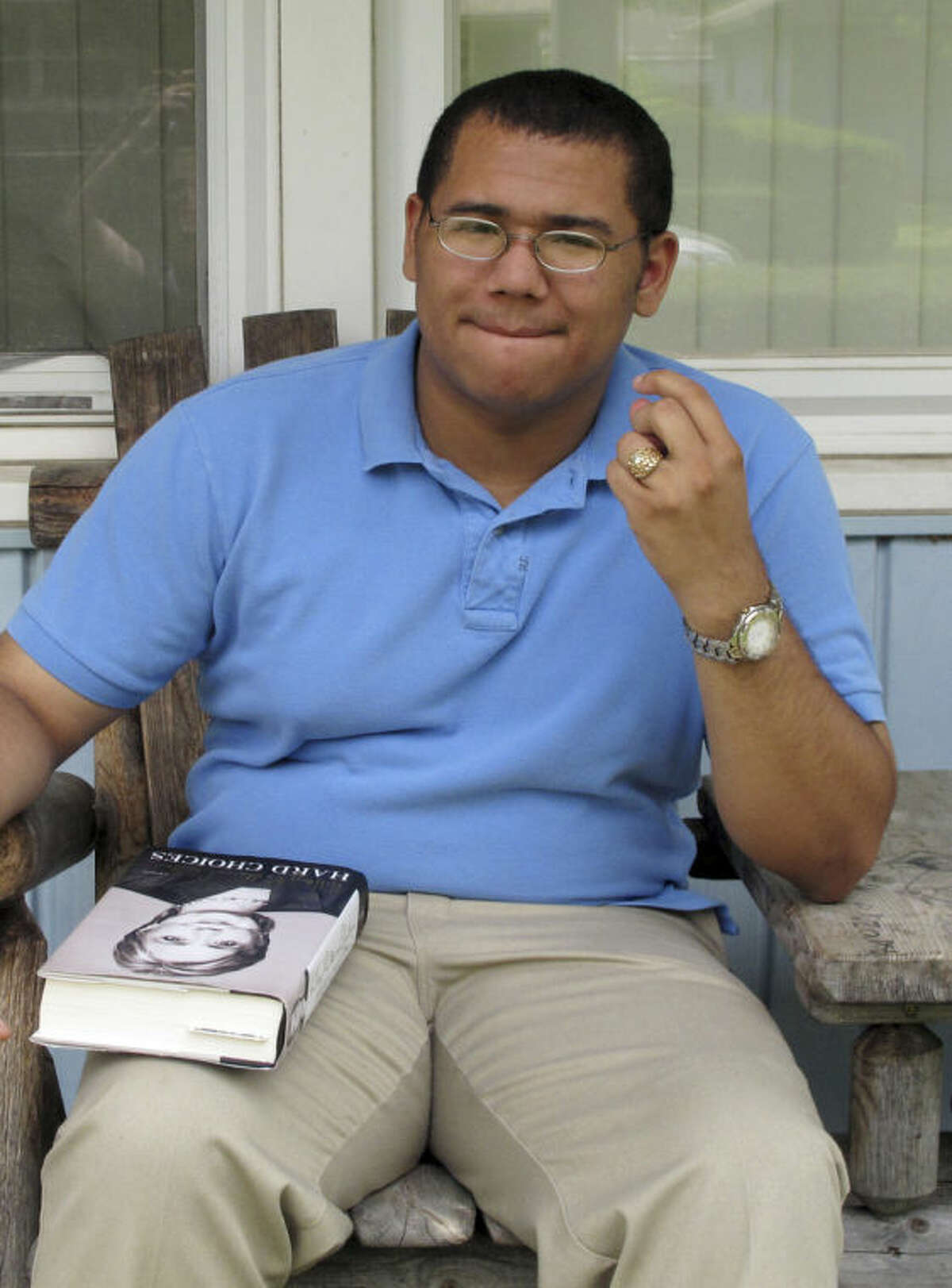 David Vernon, 18, takes a break while reading on his porch in Columbus, Ohio, on Monday, July 21, 2014. Both Republicans and Democrats are seeking voters like Vernon, a self-described moderate and an avid social media user who says he has seen a steady increase in tweets from both parties aimed at attracting younger African-American voters to get involved in political campaigns. (AP Photo)
