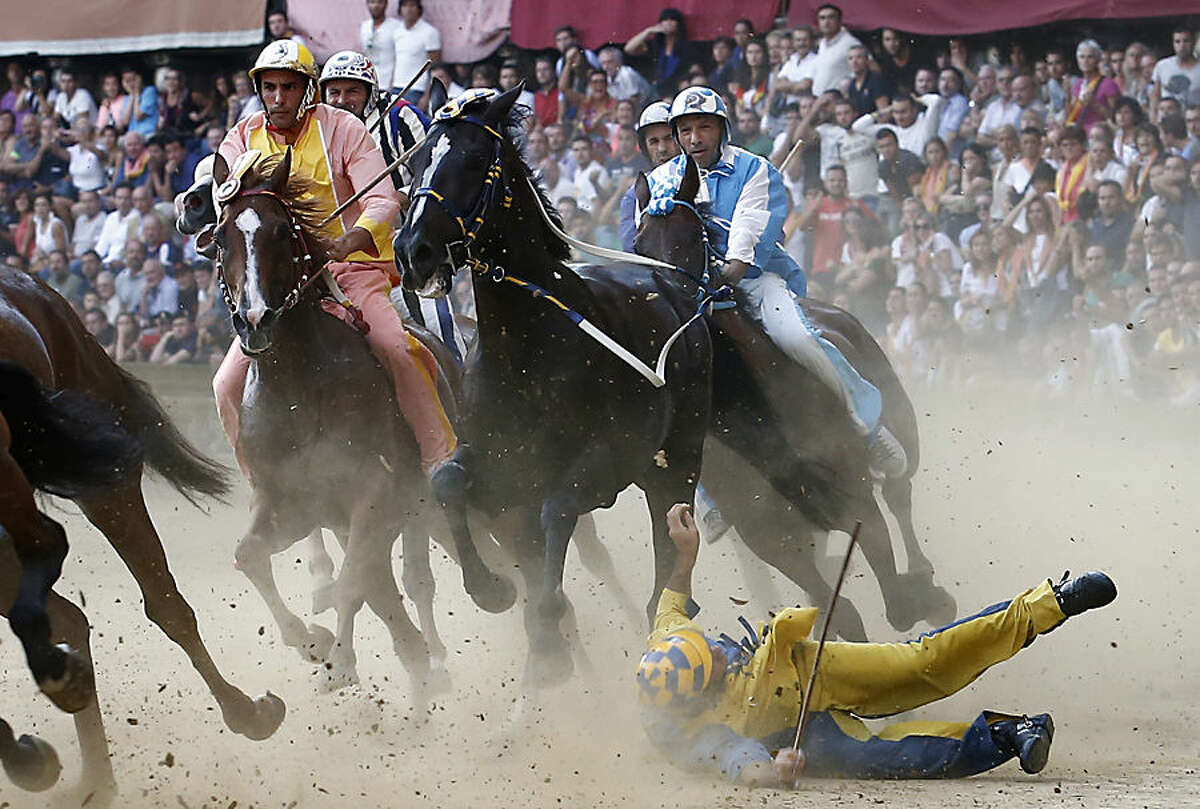 A rider falls during the ancient Palio of Siena, the famous break-neck bareback horse race run, in Siena, Italy, Monday, Aug. 17, 2015. (AP Photo/Paolo Lazzeroni)