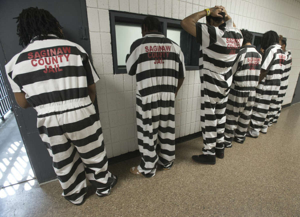 Inmates wearing new jumpsuits line up in a hallway at the Saginaw County Jail, Friday, July 18, 2014 in Saginaw, Mich. The Saginaw County Sheriff's Department has purchased new jumpsuits, with black and white stripes, for some of the inmates at the jail. (AP Photo/The Saginaw News/MLive.com, Jeff Schrier)