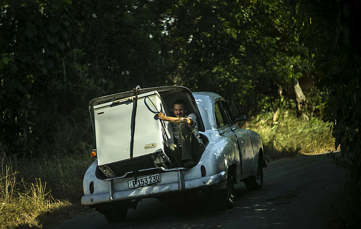 A man transports a refrigerator in the open trunk of a vintage American car outside Havana, Cuba, Monday, Aug. 17, 2015. (AP Photo/Ramon Espinosa)