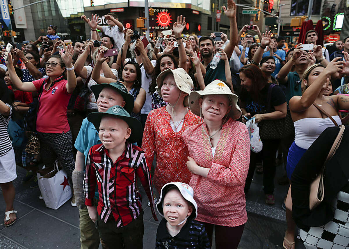 Emmanuel Rutema, Kabula Masanja, Pendo Noni, Mwigulu Magesa and Baraka Lusambo watch the Revlon live camera with a crowd of other tourists during a visit to Times Square in New York on Tuesday, July 28, 2015. People with the genetic condition of albinism, characterized by a lack of pigment, are often referred to in Tanzania as ghosts, or zero zero, which in Swahili signifies someone who is less than human. (AP Photo/Julie Jacobson)