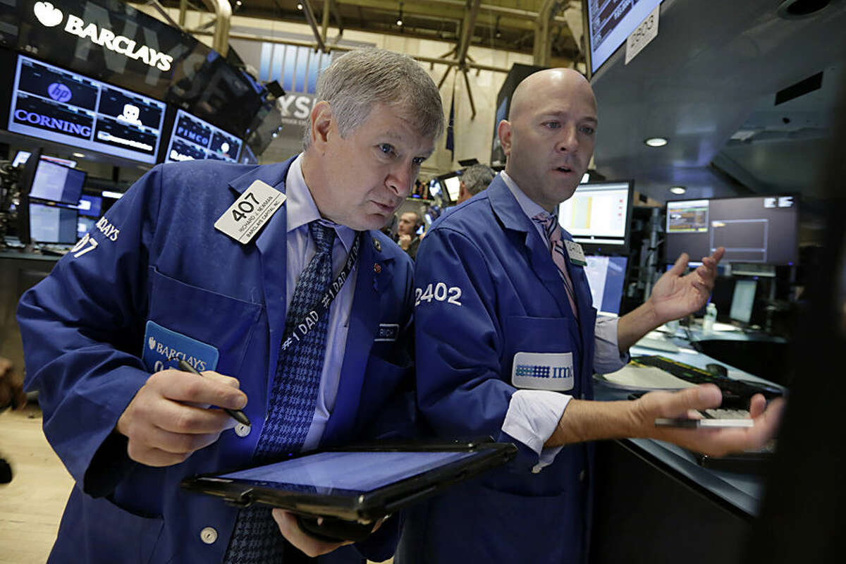 Trader Richard Newman, left, and specialist Jay Woods work on the floor of the New York Stock Exchange, Tuesday, Aug. 18, 2015. U.S. stocks are lower in early trading after China's main index had its biggest fall since late July. (AP Photo/Richard Drew)