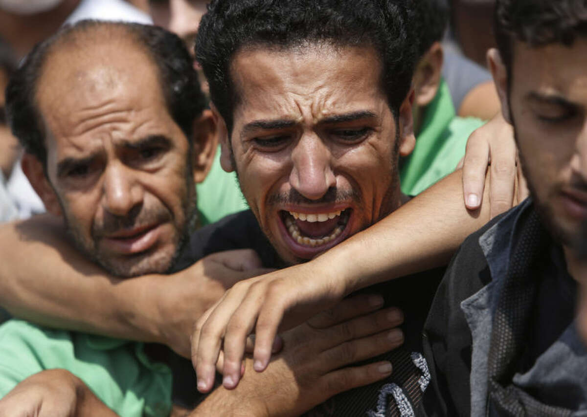 A relative bursts into tears as mourners try to comfort him as they gather around the bodies of seven members of the Kelani family, killed overnight by an Israeli strike in Gaza City, during their funeral in Beit Lahiya, northern Gaza Strip, on Tuesday, July 22, 2014. Ibrahim Kelani, 53, his wife Taghreed and their five children, were killed in the strike on a Gaza City high rise. Ibrahim's brother Saleh Kelani said Tuesday that his brother and his brother?'s children, ranging in age from four to 12, had German citizenship, while his wife had not. The family had rented the apartment in the high-rise after fleeing their home in the northern Gaza town of Beit Lahiya which came under heavy shelling by the Israeli army. (AP Photo/Lefteris Pitarakis)