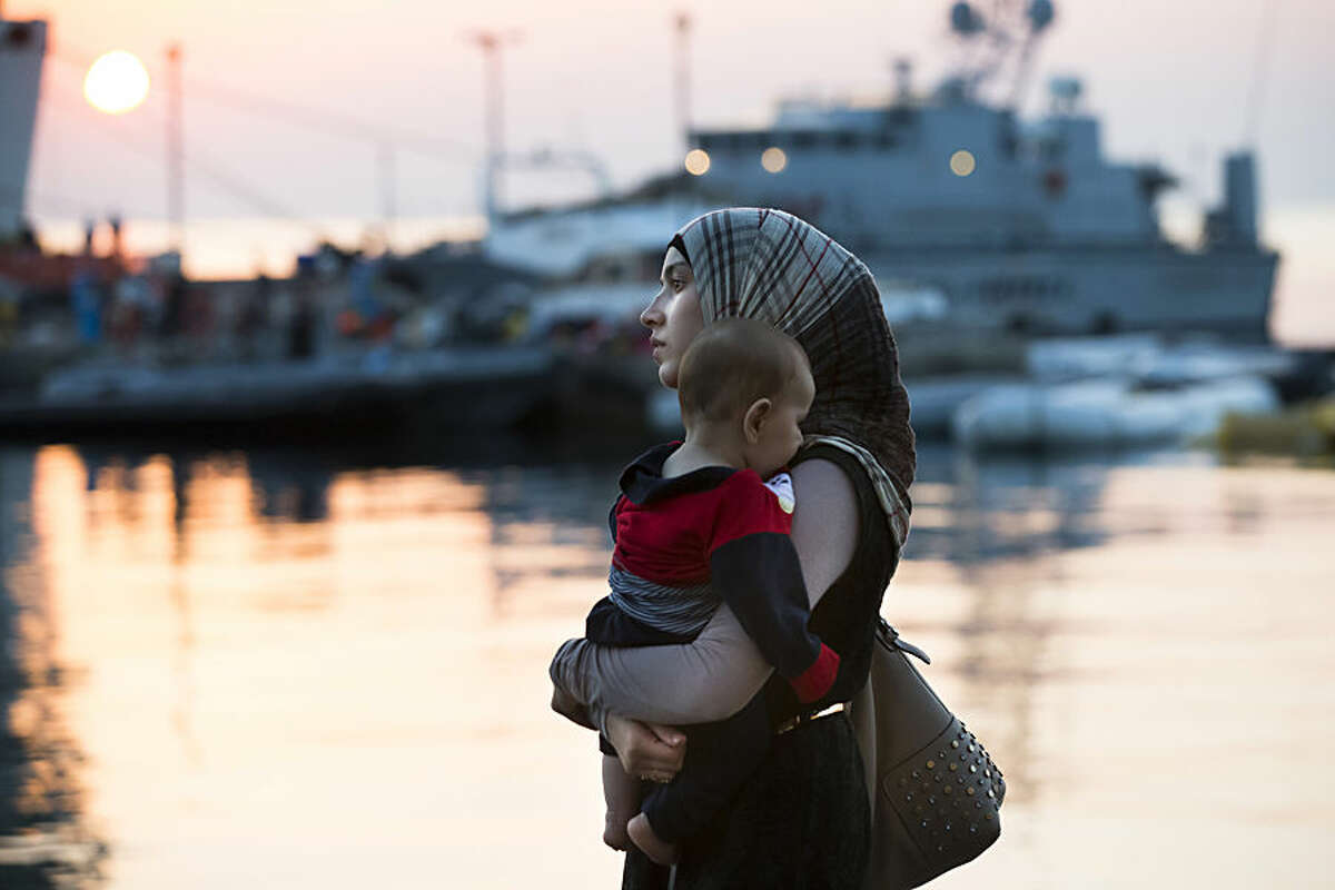 A Syrian refugee woman carrying her baby in her arms walks to the ferry Eleftherios Venizelos, which functions as a registration center and accommodation for migrants and refugees, after crossing by a boat from Turkey, in the southeastern Greek island of Kos early Monday, Aug. 17, 2015. With the lights of Kos twinkling through the darkness - beacons of hope for a new and better life - another group of migrants has set off to make a risky - but less risky than most - sea crossing and apply for asylum in Europe. (AP Photo/Alexander Zemilianichenko)