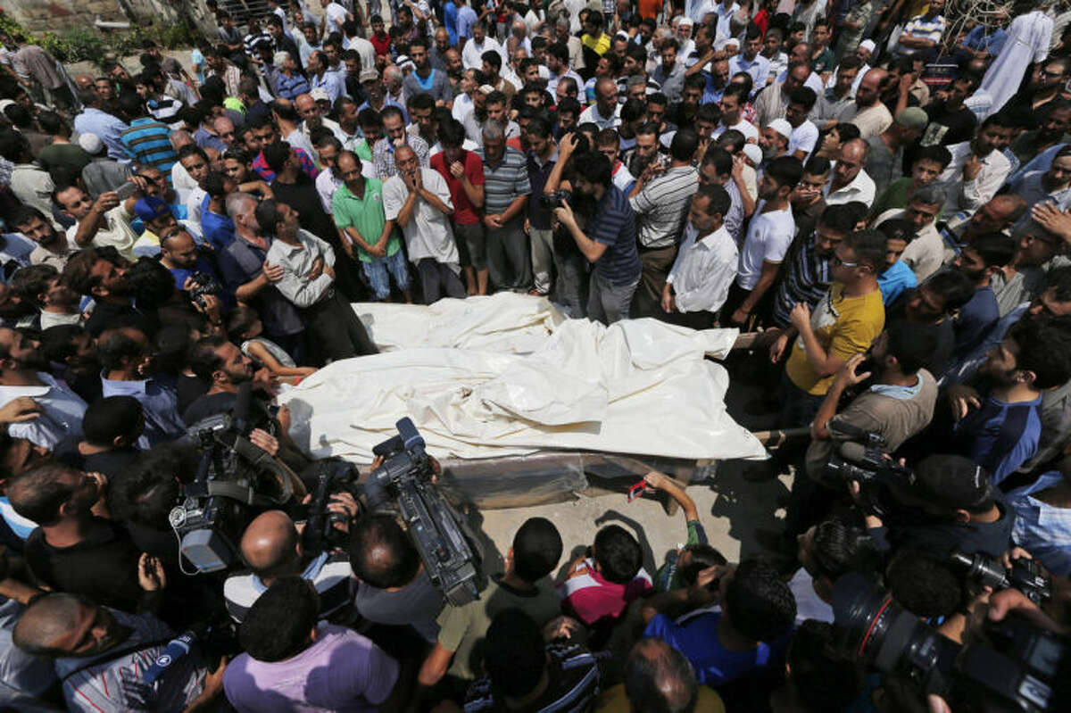 Mourners gather around the bodies of seven members of the Kelani family, killed overnight by an Israeli strike in Gaza City, during their funeral in Beit Lahiya, northern Gaza Strip, on Tuesday, July 22, 2014. Ibrahim Kelani, 53, his wife Taghreed and their five children, were killed in the strike on a Gaza City highrise. Ibrahim's brother Saleh Kelani said Tuesday that his brother and his brother?'s children, ranging in age from four to 12, had German citizenship, while his wife had not. The family had rented the apartment in the high-rise after fleeing their home in the northern Gaza town of Beit Lahiya which came under heavy shelling by the Israeli army. (AP Photo/Lefteris Pitarakis)