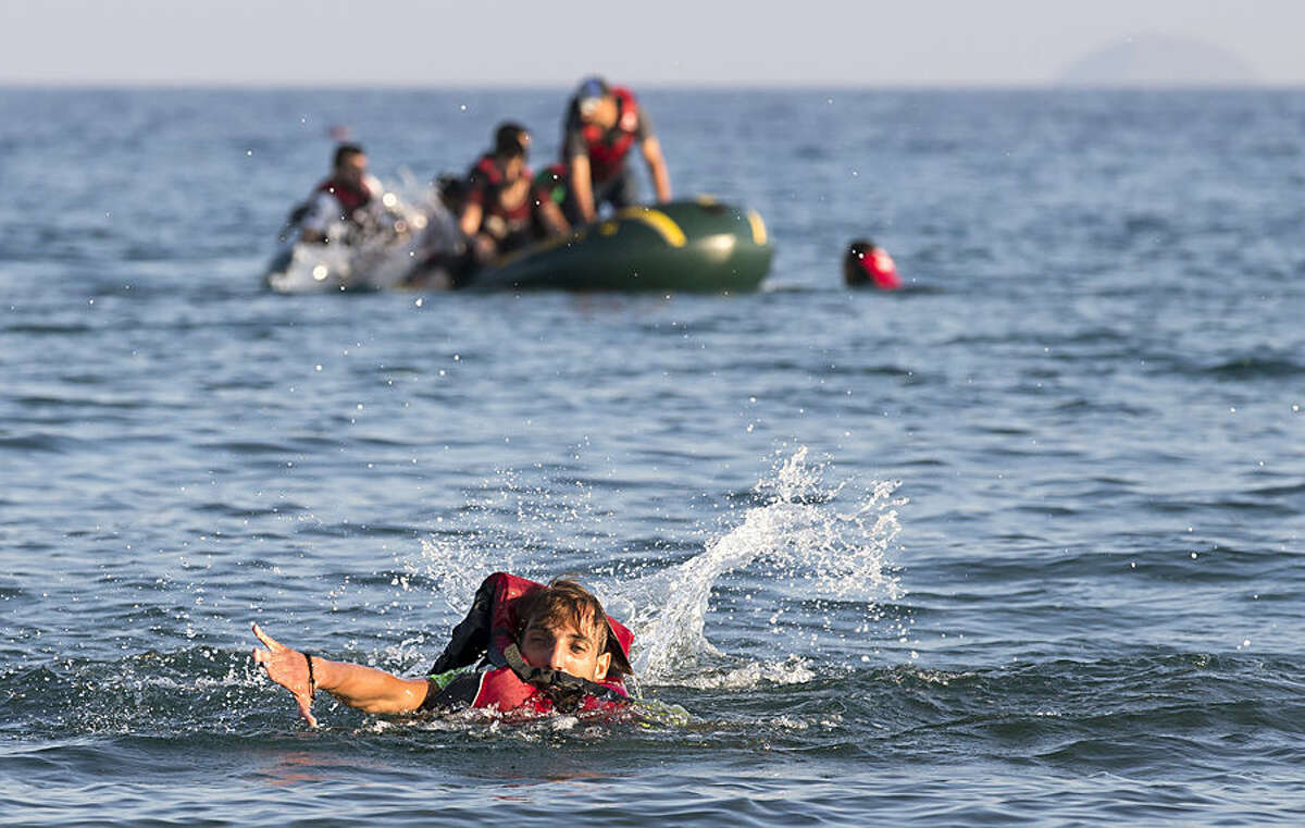 Migrants and refugees, one of them swims, arrive after crossing from Turkey, at the southeastern island of Kos, Greece, Monday, Aug. 17, 2015. With the lights of the Greek island of Kos twinkling through the darkness, beacons of hope for a new and better life, another group of migrants has come through this wealthy tourist town to make a risky, but less risky than most, sea crossing and apply for asylum in Europe. (AP Photo/Alexander Zemlianichenko)