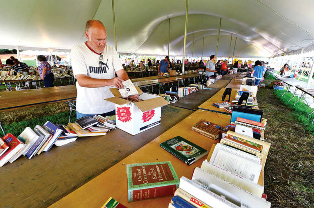 Hour photo / Erik Trautmann James Young loads up on half price books on the last day of the Westport Public Library BOOKstravaganza: The Annual Gigantic Summer Book Sale at Jesup Green Monday.