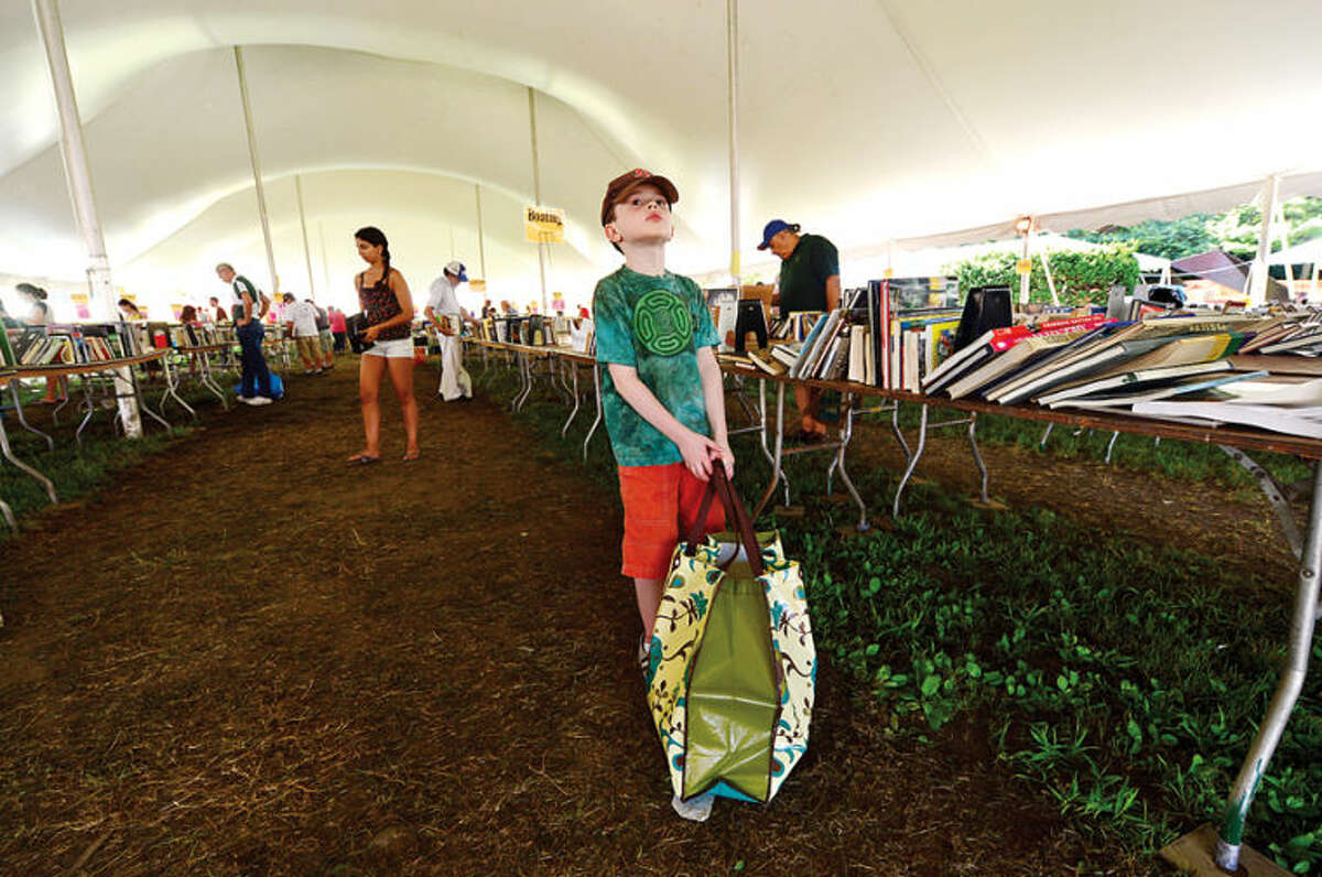 Hour photo / Erik Trautmann 8 year old Tom Sheetz loads up on half price books on the last day of the Westport Public Library BOOKstravaganza: The Annual Gigantic Summer Book Sale at Jesup Green Monday.
