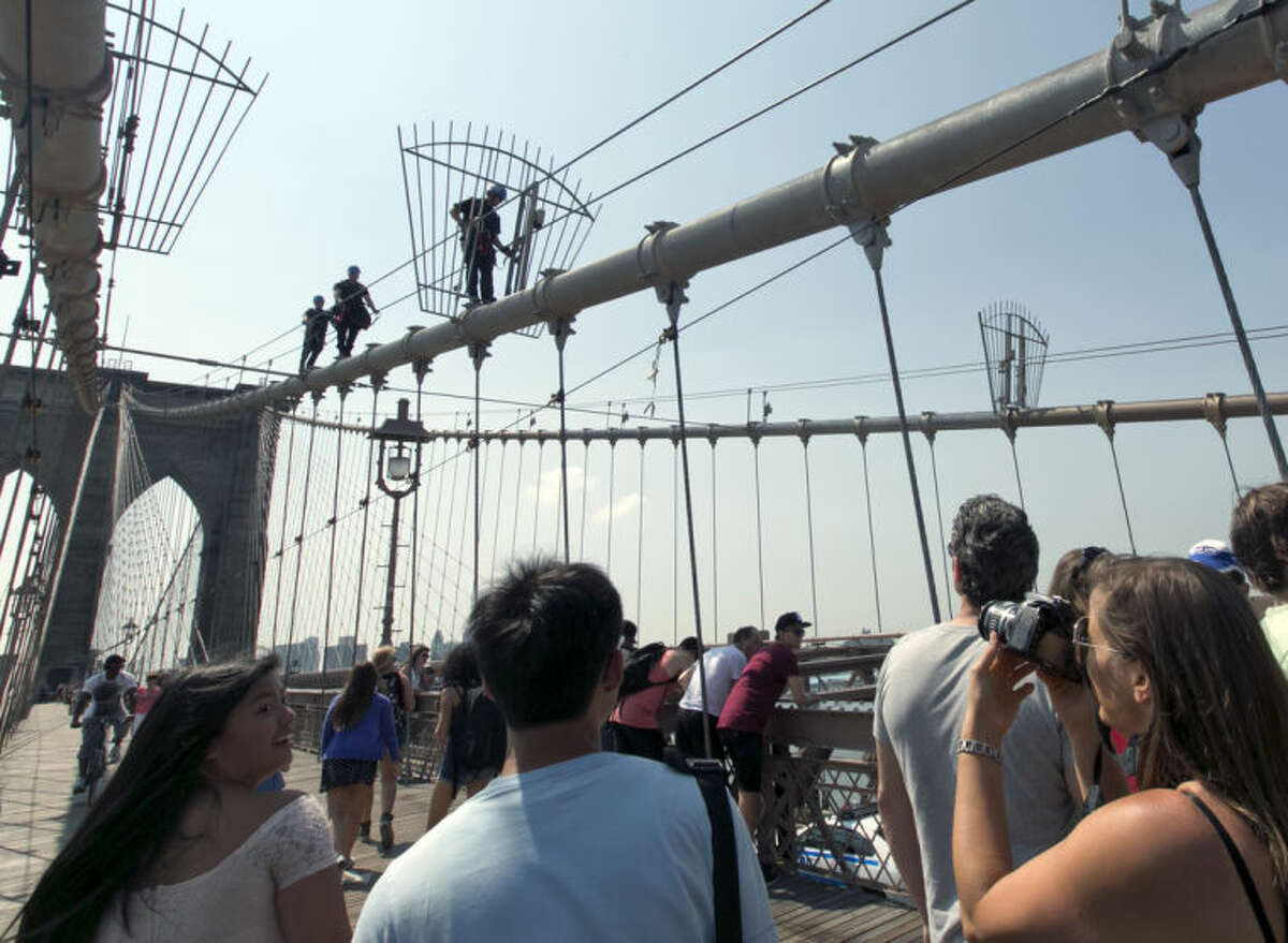"""Pedestrains watch a New York City Police officers descend a cable of New York's Brooklyn Bridge, after they lowered a white flag that was flying atop the bridge's west tower, Tuesday, July 22, 2014. Someone replaced two American flags on the bridge with mysterious white flags. The white flags, international symbols of surrender, fluttered from poles on the stone supports that hold cables above the bridge connecting Brooklyn and Manhattan. An entity called Bike Lobby tweeted Tuesday that it hoisted the flags to signal ?""""surrender of the Brooklyn Bridge bicycle path to pedestrians.?"""" (AP Photo/Richard Drew)"""