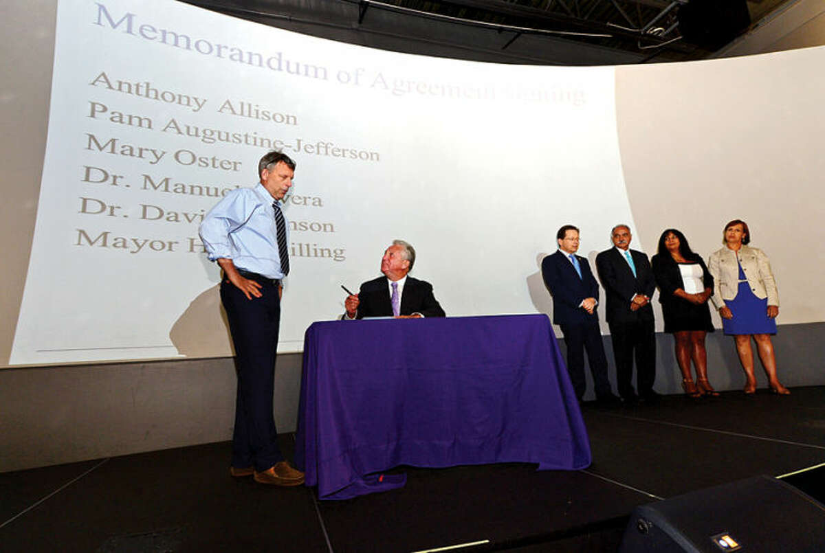 """Hour photo / Erik Trautmann Norwalk ACTS members, Anthony Allison, Executive Director, Norwalk ACTS; Mayor Harry Rilling, Dr. Manuel J. Rivera, Superintendent of Norwalk Public Schools; Dr. David Levinson, President, Norwalk Community College; Pam Augustine-Jefferson, Instructional Specialist, Early Childhood, Norwalk Public Schools; Mary Oster, Early Childhood Coordinator, City of Norwalk sign a """"Memorandum of Understanding"""" to ensure a coordinated and integrated coalition of resources to dramatically improve educational, social and emotional growth and physical health outcomes for Norwalk's children during a press event follwing ACTS monthly meeting."""