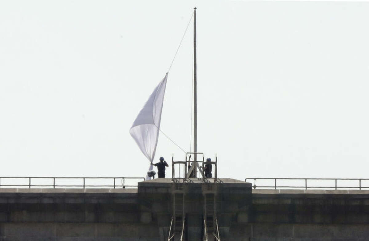 """New York City Police officers lower a white flag flying atop the west tower of New York's Brooklyn Bridge, Tuesday, July 22, 2014. Someone replaced two American flags on the bridge with mysterious white flags. The white flags, international symbols of surrender, fluttered from poles on the stone supports that hold cables above the bridge connecting Brooklyn and Manhattan. An entity called Bike Lobby tweeted Tuesday that it hoisted the flags to signal ?""""surrender of the Brooklyn Bridge bicycle path to pedestrians.?"""" (AP Photo/Richard Drew)"""