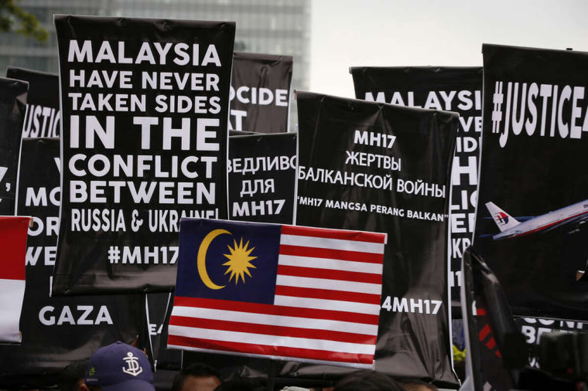 Banners are held up by protesters during a protest in front of Ukraine embassy in Kuala Lumpur, Malaysia, Tuesday, July 22, 2014. Protesters marched on the Russian embassy and Ukraine embassy in Kuala Lumpur on Tuesday, waving placards and demanding justice for the victims of the Malaysia Airlines flight that was shot down over Ukraine last week. (AP Photo/Vincent Thian)