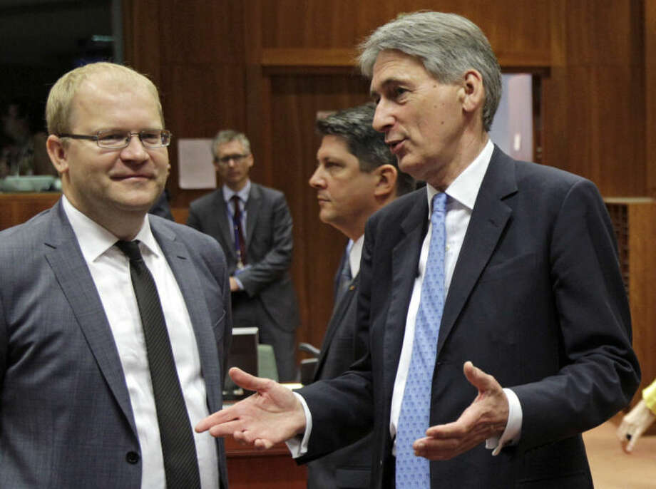 British Foreign Secretary Philip Hammond, right, talks with Estonia's Foreign Minister Urmas Paet during an EU foreign ministers council at the European Council building in Brussels, Tuesday, July 22, 2014. European Union foreign ministers are meeting to consider further sanctions against Russia because of the downing of a Malaysian jetliner, with Britain and some other countries demanding much tougher measures. (AP Photo/Yves Logghe)