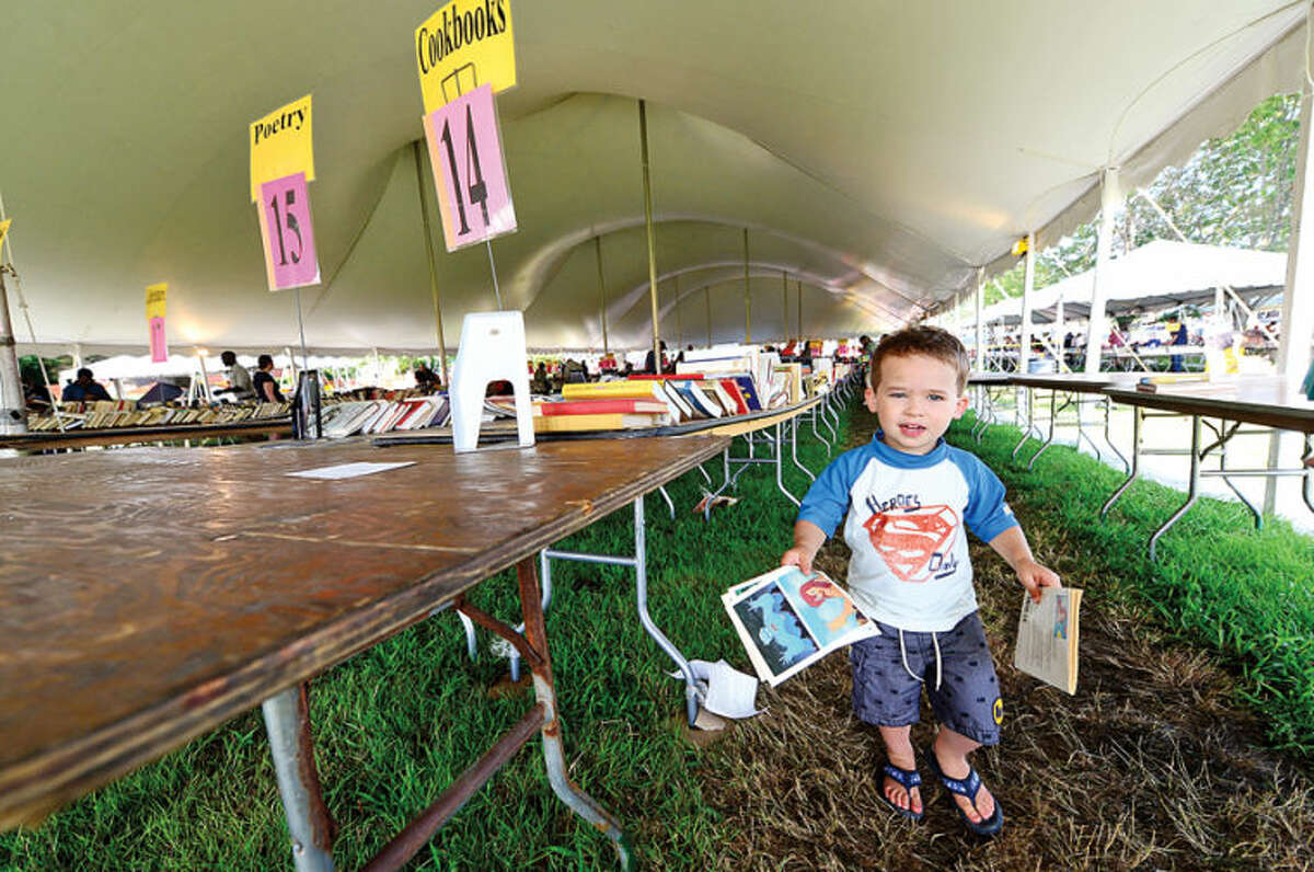 Hour photo / Erik Trautmann Wesport resident 2 year old Jacob Hantler finds some half price books on the last day of the Westport Public Library BOOKstravaganza: The Annual Gigantic Summer Book Sale at Jesup Green Monday.