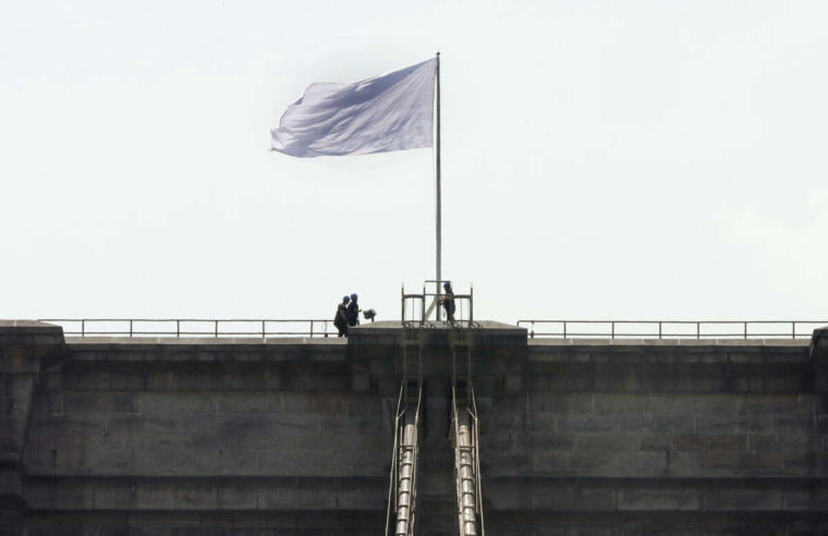 """New York City Police officers stand at the base of a white flag flying atop the west tower of New York's Brooklyn Bridge, Tuesday, July 22, 2014. Someone replaced two American flags on the bridge with mysterious white flags. The white flags, international symbols of surrender, fluttered from poles on the stone supports that hold cables above the bridge connecting Brooklyn and Manhattan. An entity called Bike Lobby tweeted Tuesday that it hoisted the flags to signal ?""""surrender of the Brooklyn Bridge bicycle path to pedestrians.?"""" (AP Photo/Richard Drew)"""