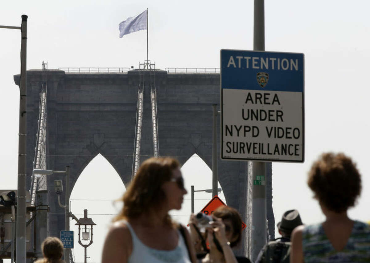 """A white flag flies atop the west tower of New York's Brooklyn Bridge, Tuesday, July 22, 2014. Someone replaced two American flags on the bridge with mysterious white flags. The white flags, international symbols of surrender, fluttered from poles on the stone supports that hold cables above the bridge connecting Brooklyn and Manhattan. An entity called Bike Lobby tweeted Tuesday that it hoisted the flags to signal ?""""surrender of the Brooklyn Bridge bicycle path to pedestrians.?"""" (AP Photo/Richard Drew)"""