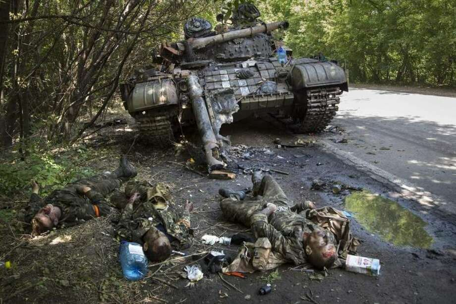 EDITORS NOTE GRAPHIC CONTENT - Bodies of crew members lie next to a destroyed Ukrainian tank in the northern outskirts of city of Donetsk, eastern Ukraine Tuesday, July 22, 2014. The soldiers were reportedly killed in fighting between rebels and government forces Monday. (AP Photo/Dmitry Lovetsky)