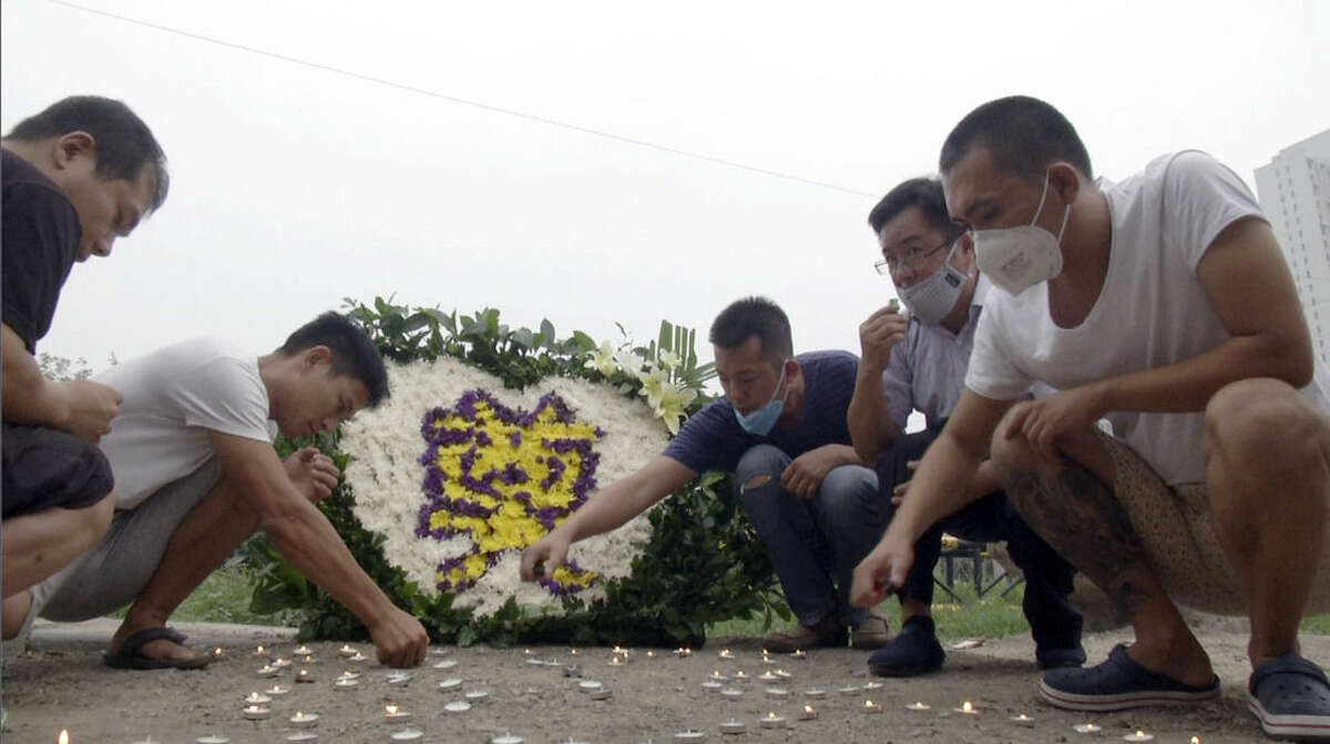 Residents of the Harbour City apartment complex light candles at a memorial near their building for victims of the Tianjin blasts in northeastern China's Tianjin municipality Tuesday, Aug. 18, 2015. Thunderstorms on Tuesday complicated recovery efforts from last week's massive deadly explosions at a warehouse in China's Tianjin port that exposed dangerous chemicals - including some that could become flammable on contact with water. (AP Photo/Paul Traynor)
