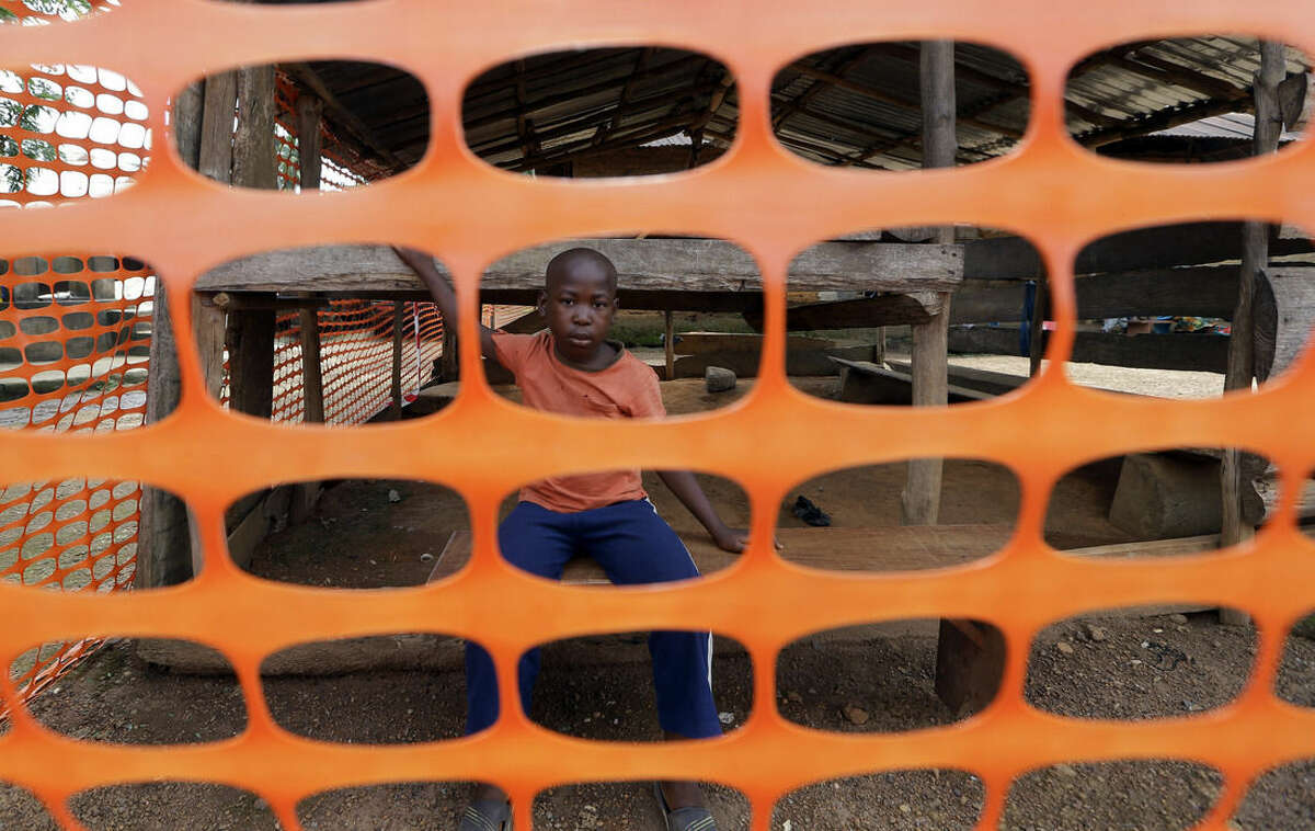 In this photo taken Friday, Aug. 14, 2015, a child waits to be released from quarantine as police officers stand guard while people dance while they are finally released from Ebola quarantine by Sierra Leone President Ernest Bai Koroma, in the village of Massessehbeh on the outskirts of Freetown, Sierra Leone. Five long months after a man traveled to his hometown for festivities marking the end of Ramadan, and died suddenly from Ebola, President Koroma has come to cut down the fencing to mark the formal end of Sierra Leone's largest remaining Ebola quarantine. (AP Photo/Sunday Alamba)