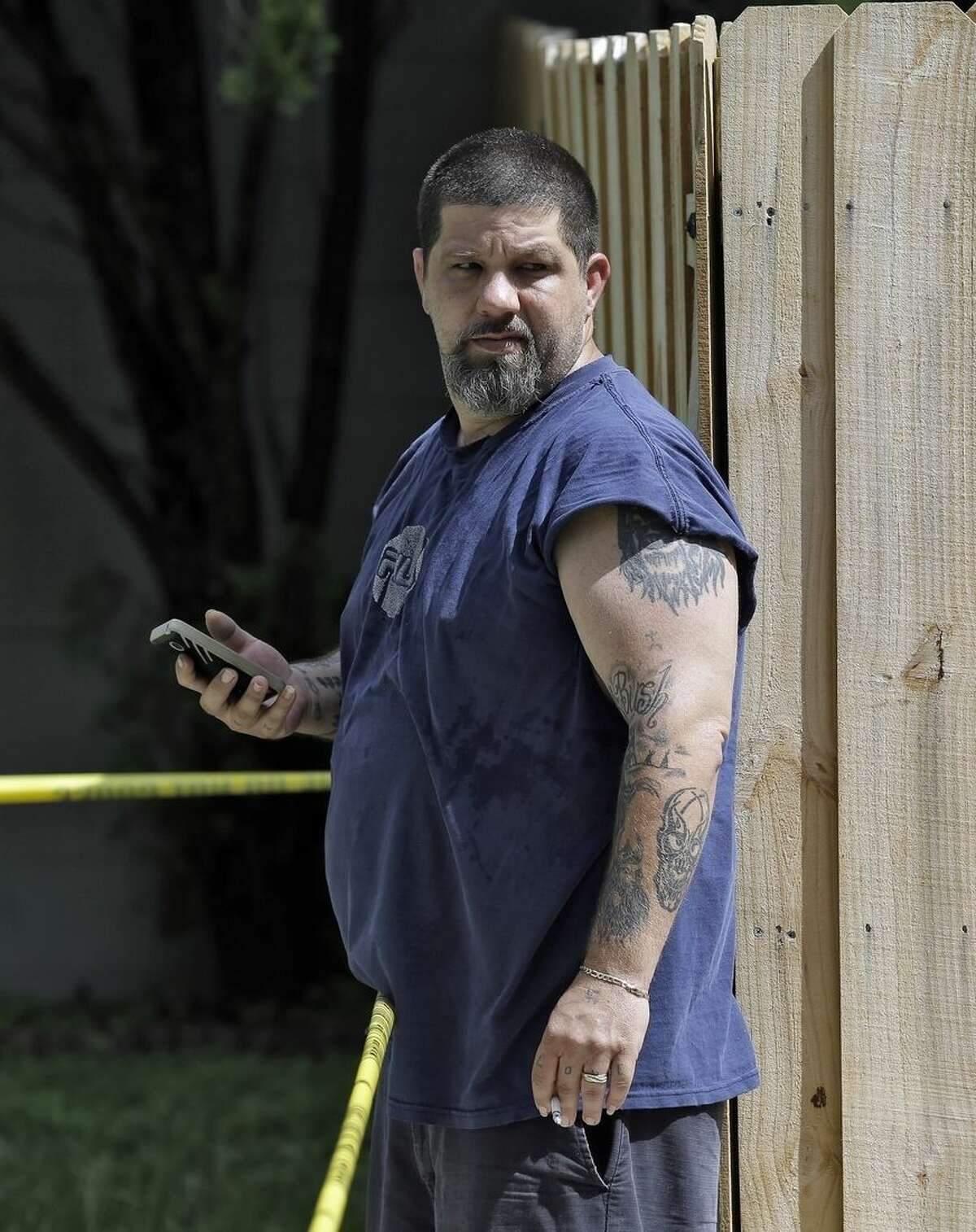 Jeremy Bush watches as members of the Hillsborough County Code Enforcement survey the property where a sinkhole reopened, Wednesday, Aug. 19, 2015, in Seffner, Fla. The sinkhole reopened in the exact same location where one swallowed Jeremy's brother Jeffrey Bush, as he slept in his bed more than two years ago. The new hole is 17 feet wide by 20 feet deep, according to code enforcement director Ron Spiller. In March 2013, Jeffrey Bush was asleep in his bedroom on the property when the floor collapsed and he fell in. His body was never recovered. (AP Photo/Chris O'Meara)