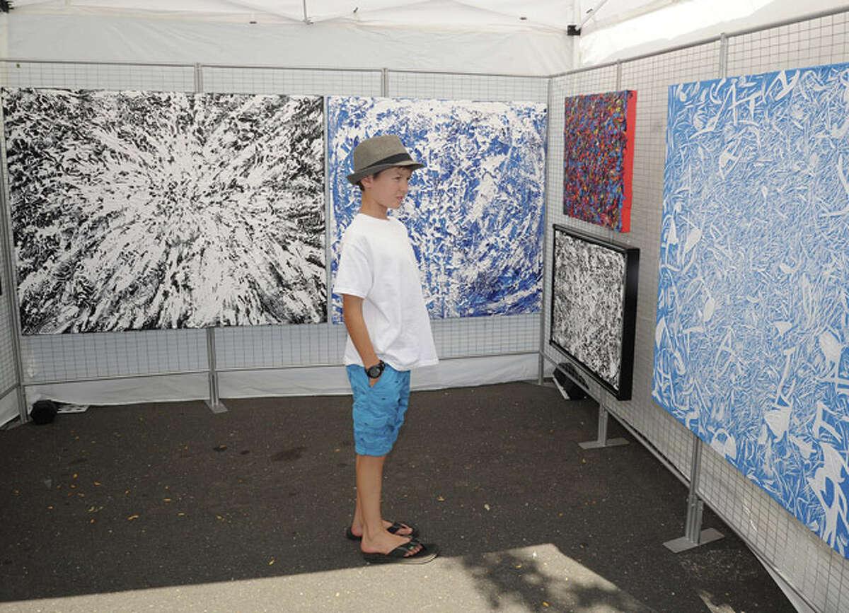 Graham Olenstein 11, admiring paintings Sunday at the Westport Arts Festival. Hour photo/Matthew Vinci