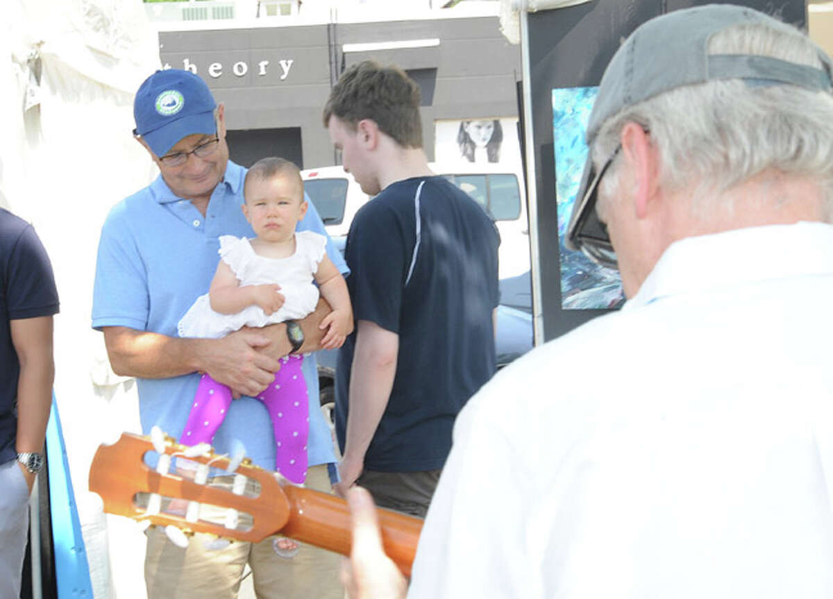 Brian Bomberger and his granddaughter Pela 1, take in some live music Sunday at the Westport Arts Festival. Hour photo/Matthew Vinci