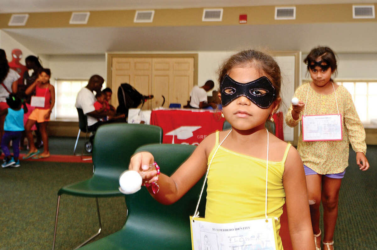Hour photo / Erik Trautmann Sage Smith, 5, and Ariana Mesa, 7, look to complete the superhero mission obstacle course during the Back to School Celebration for children in grades K - 5 at the SoNo Library Saturday sponsored by the library and ConnCAN (The Connecticut Coalition for Achievement Now).