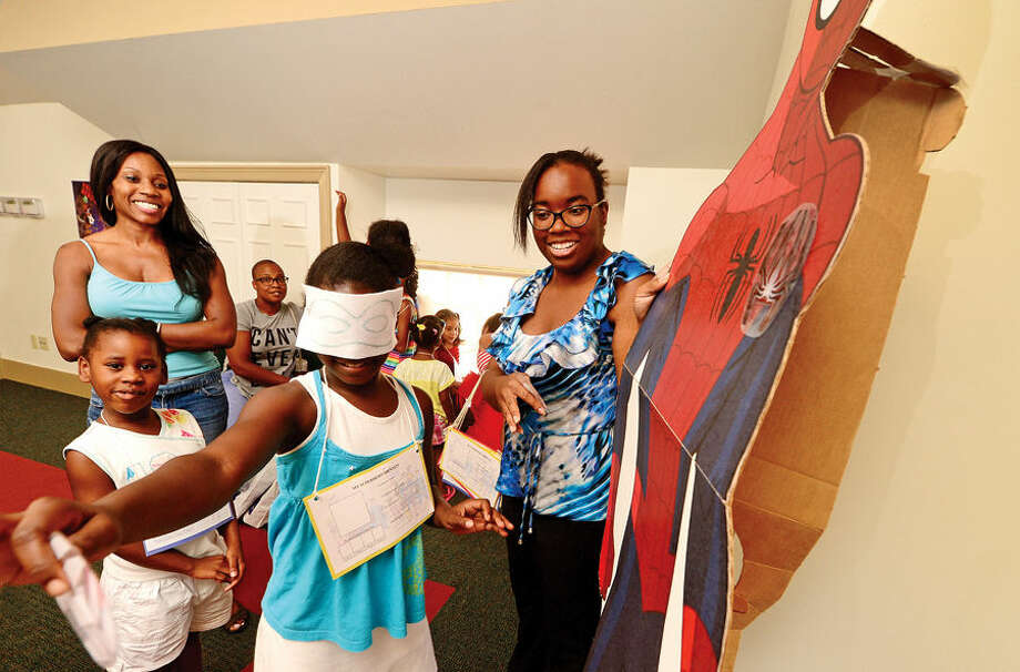 """Hour photo / Erik Trautmann South Norwalk Branch Library Clerk Raven McFadden, right, helps Alexa Spencer, 8, with the superhero mission, """"Pin the Spider on Spider-Man"""", while her sister Alana Spencer, 5, and mother, Crystal McGee, look on during a Back to School Celebration for children in grades K - 5 at the SoNo Library Saturday sponsored by the library and ConnCAN (The Connecticut Coalition for Achievement Now)."""