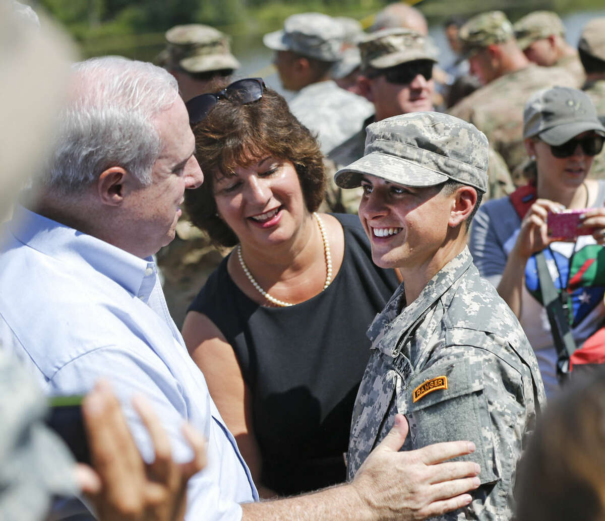 """U.S. Army First Lt. Shaye Haver, right, smiles after receiving her """"Ranger Tabs"""" from an unidentified man after an Army Ranger school graduation ceremony Friday, Aug. 21, 2015, at Fort Benning, Ga. Haver and Capt. Kristen Griest became the first female graduates of the Army's rigorous Ranger School, putting a spotlight on the debate over women in combat. (AP Photo/John Bazemore)"""