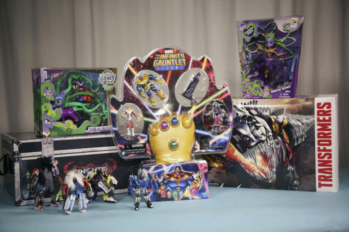 """This Friday, July 18, 2014 photo shows exclusive, collectible toys available from Hasbro at 2014 Comic-Con, in San Diego. Marvel?'s ?""""The Thanos Imperitive?"""" action figure set, at center with a foam Infinity Gauntlet, is seen with, from left, the Transformers ?""""Knights of Unicron?"""" collection, My Little Pony Mane-iac Mayhem figure, Transformers Dinobots collection and My Little Pony Equestria Girls figure. Several toy makers and publishers are offering collectible toys and books at the annual pop-culture celebration, which kicks off Thursday, July 24, 2014, in San Diego. (AP Photo/Nick Ut)"""