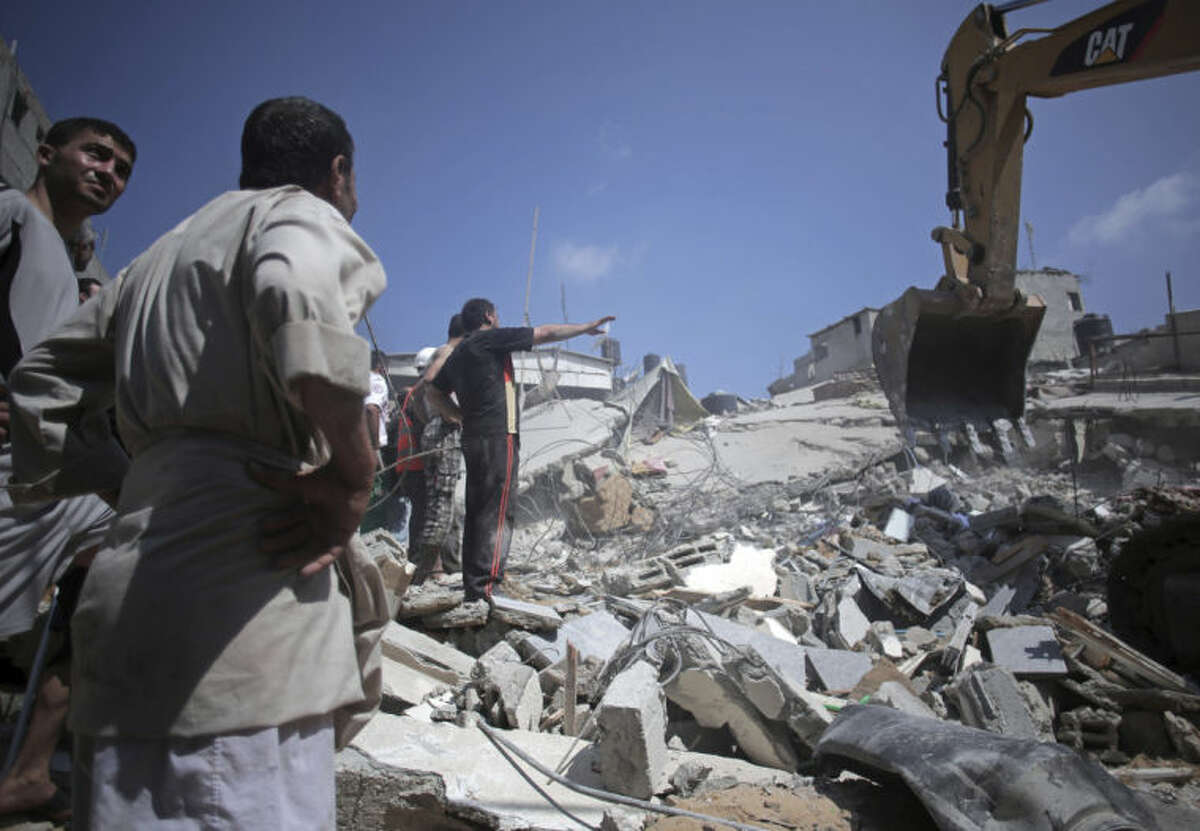 Palestinian rescuers search for bodies and survivors in the rubble of homes which were destroyed by an Israeli missile strike, in Gaza City, Monday, July 21, 2014. On Sunday, the first major ground battle in two weeks of Israel-Hamas fighting exacted a steep price, killing scores Palestinians and over a dozen Israeli soldiers and forcing thousands of terrified Palestinian civilians to flee their devastated Shijaiyah neighborhood, which Israel says is a major source for rocket fire against its civilians. (AP Photo/Khalil Hamra)