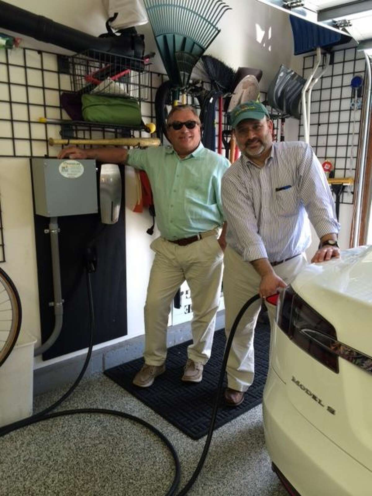 Photo:Ed Ingalls, owner of CT Electric Car, a division of Newington Electric, visits with Tesla electric vehicle owner Seth Diamond after the installation of a car charging station at his Glastonbury, CT home. CT Electric Carhas been selected as one of Tesla's recommended car charging station installers.
