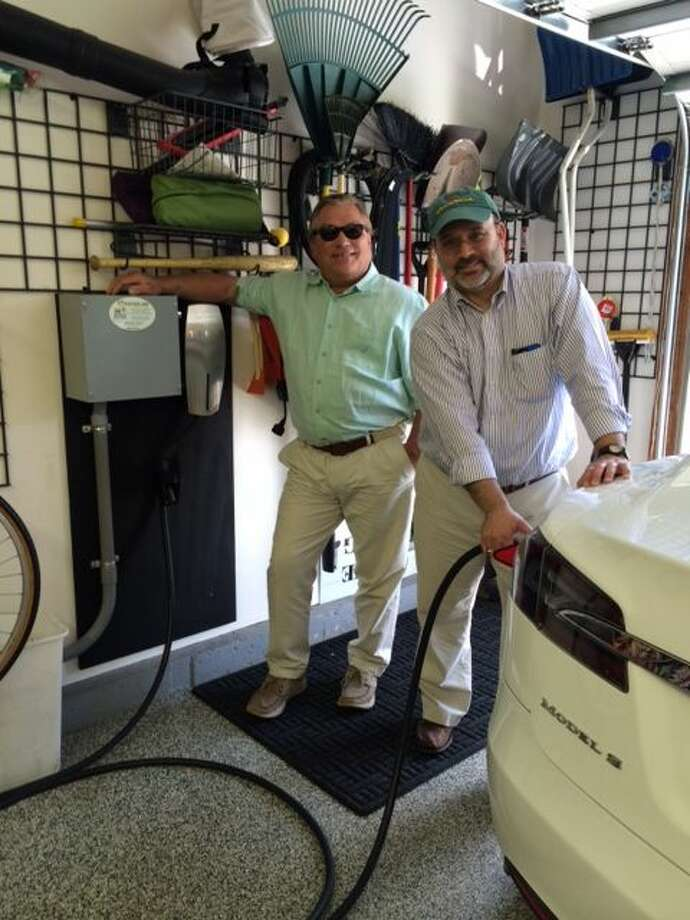 Photo: Ed Ingalls, owner of CT Electric Car, a division of Newington Electric, visits with Tesla electric vehicle owner Seth Diamond after the installation of a car charging station at his Glastonbury, CT home. CT Electric Car has been selected as one of Tesla's recommended car charging station installers.